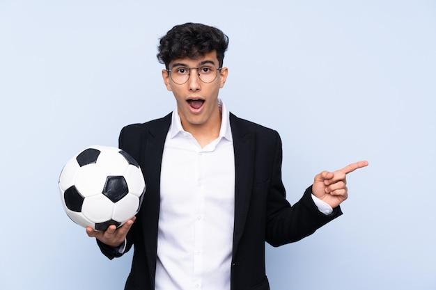 Argentinischer fußballtrainer über lokalisierter blauer wand überrascht und seite zeigend