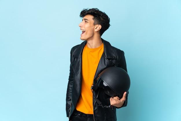 Argentinischer mann mit einem motorradhelm, der in seitlicher position lacht