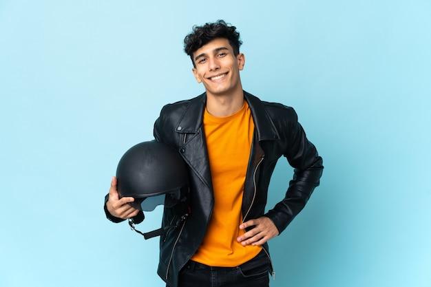 Argentinischer mann mit einem motorradhelm, der mit den armen an der hüfte aufwirft und lächelt