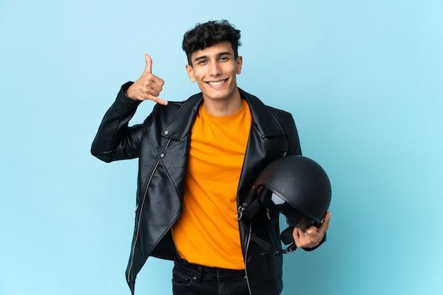 Argentinischer mann mit einem motorradhelm, der telefongeste macht. rufen sie mich zurück zeichen
