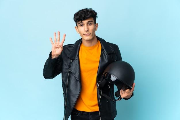 Argentinischer mann mit einem motorradhelm glücklich und zählt vier mit den fingern