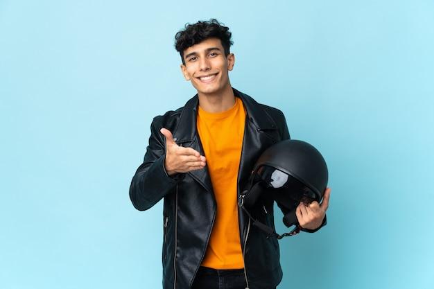 Argentinischer mann mit einem motorradhelm händeschütteln für das schließen eines guten geschäfts