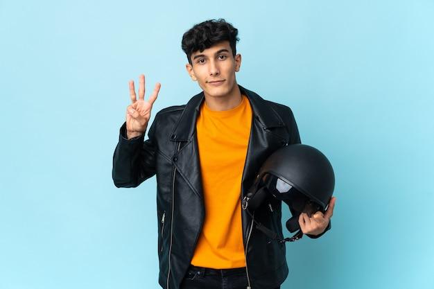 Argentinischer mann mit motorradhelm glücklich und zählt drei mit den fingern