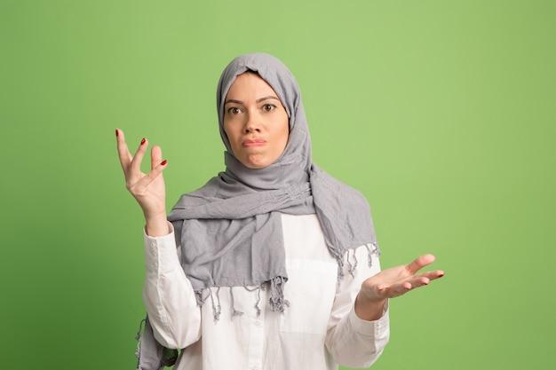 Argumentieren sie, argumentieren sie konzept.arab frau im hijab. porträt des mädchens, das im grünen studio aufwirft.