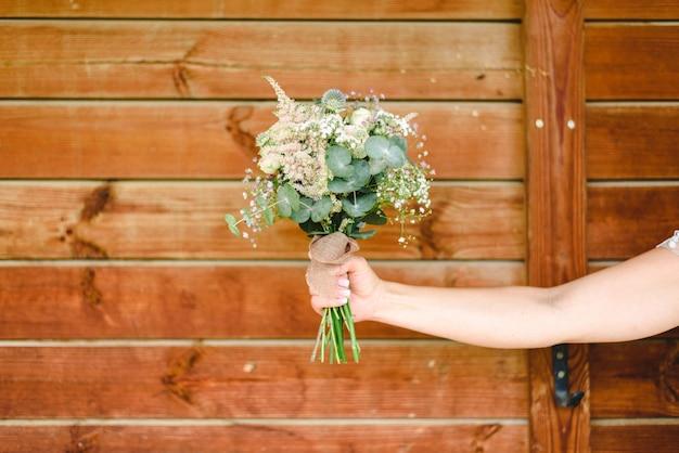 Arm der frau ihren brautblumenstrauß mit hölzernem hintergrund halten