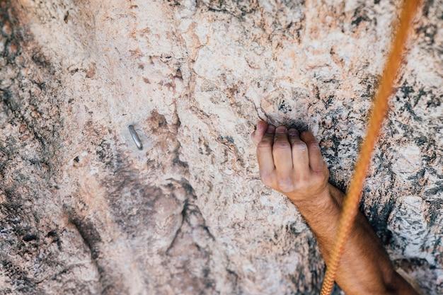 Arm des bergsteigers am felsen