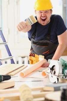 Arm des lächelnden arbeiters halten pinselporträt