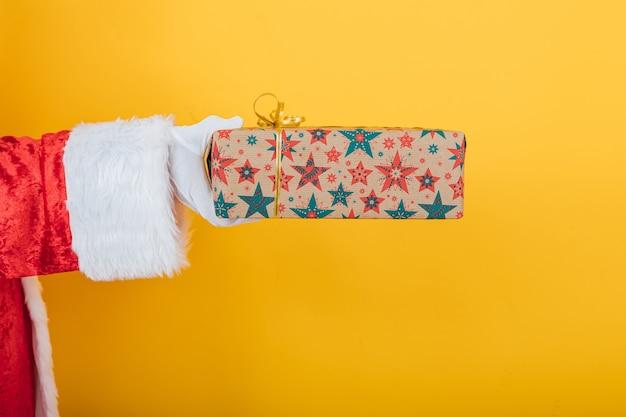 Arm des weihnachtsmannes hält ein geschenk von der linken seite auf gelb