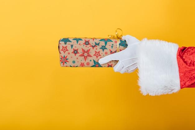 Arm des weihnachtsmannes hält ein geschenk von der rechten seite auf gelb