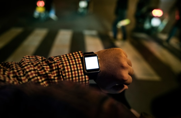 Arm mit digitaler armbanduhr in der nacht