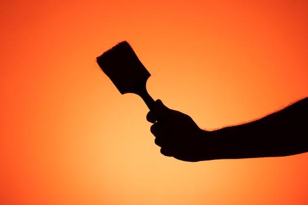 Arm umklammert einen gebrauchten pinsel auf farbigem hintergrund. silhouettenfotografie