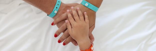 Armbänder werden an kinder- und erwachsenenhand getragen und zusammengefaltet