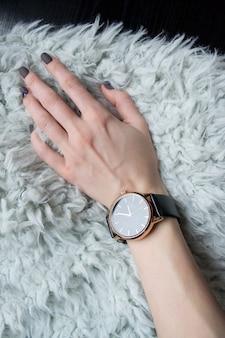 Armbanduhr am weiblichen handgelenk.