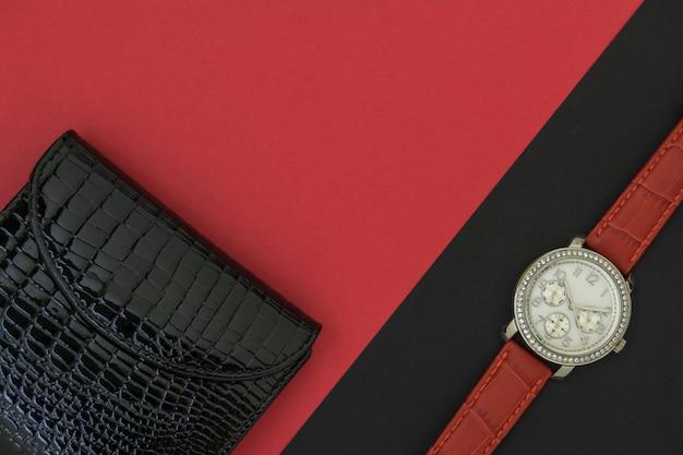 Armbanduhr der frauen auf schwarzem hintergrund. die geldbörse der schönen schwarzen frauen auf einem roten backgroun