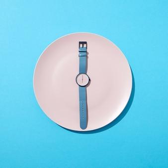 Armbanduhr mit sechs uhr und blauer biegung auf einem weißen teller an einer blauen wand. zeit zum abnehmen, esskontrolle oder diätkonzept. draufsicht.