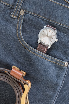 Armbanduhr und ledergürtel an jeans