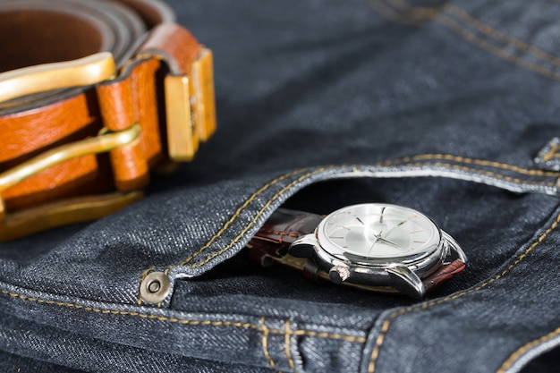 Armbanduhr und ledergürtel auf jeans