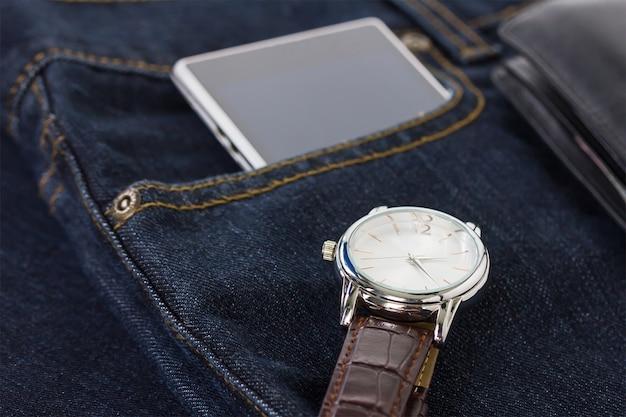 Armbanduhr und smartphone auf denimjeans