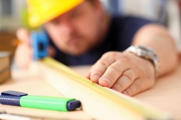 Arme des arbeiters, der holzstangen-nahaufnahme misst