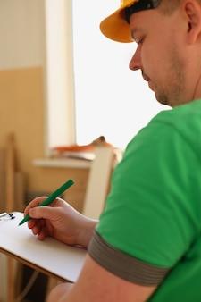 Arme des arbeiters, der notizen auf zwischenablage mit grünem stift macht