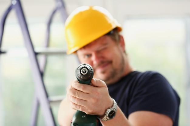 Arme des arbeiters unter verwendung der elektrischen bohrer nahaufnahme