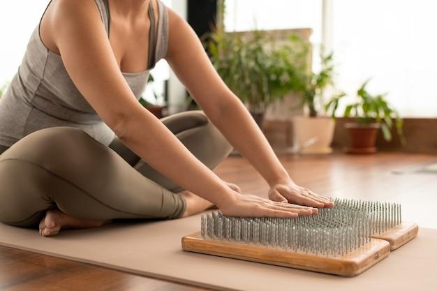 Arme einer jungen frau mit gekreuzten beinen in aktivkleidung, die auf einer matte vor yoga-pads mit nägeln sitzt und während des trainings die handflächen darauf hält