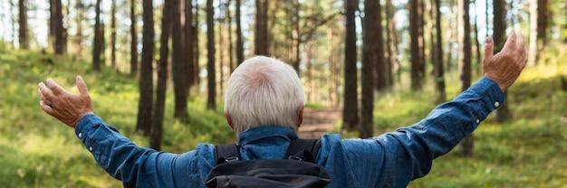 Arme weit offener älterer mann, der natur erforscht