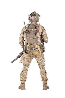 Armeesoldat in tarnuniform und kampfhelm, ausgestatteter taktischer radiosender mit headset, rucksack tragen, munition, seil, granaten in hüfttasche tragen, rückwärts stehend isoliertes studioshooting
