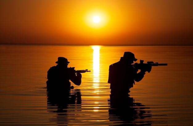 Armeesoldaten mit gewehren orange sonnenuntergangschattenbild in aktion während des überfalls, der fluss im wasser überquert