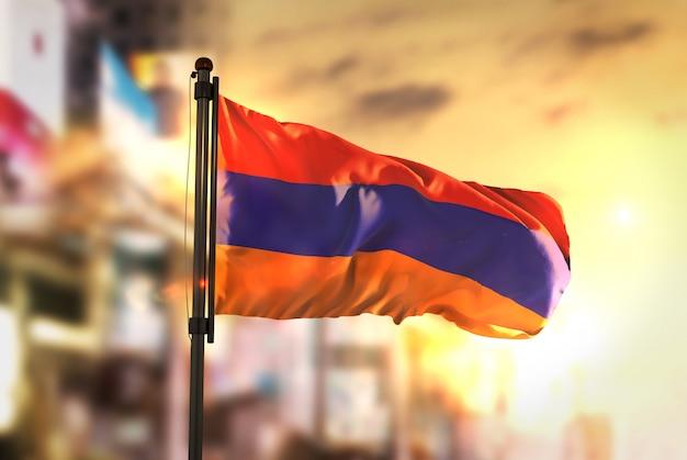 Armenien-flagge gegen stadt verschwommen hintergrund bei sonnenaufgang hintergrundbeleuchtung