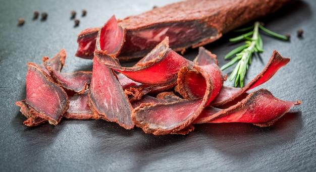 Armenische basturma. rindfleisch gepökelt und gewürzt. bioprodukte auf einem holztisch