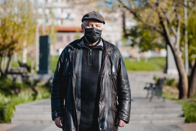 Armenischer alter mann mit dem schwarzen hut, der medizinische maske in der straße im frühjahr trägt und vorne schaut