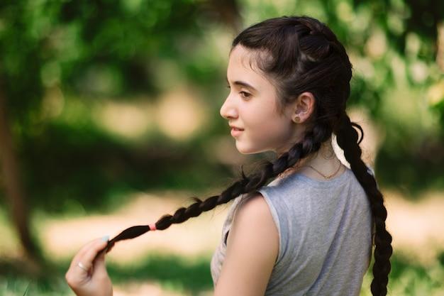 Armenisches niedliches mädchen, das haargeflecht im bunten grünen garten im sommer und lächelnd hält