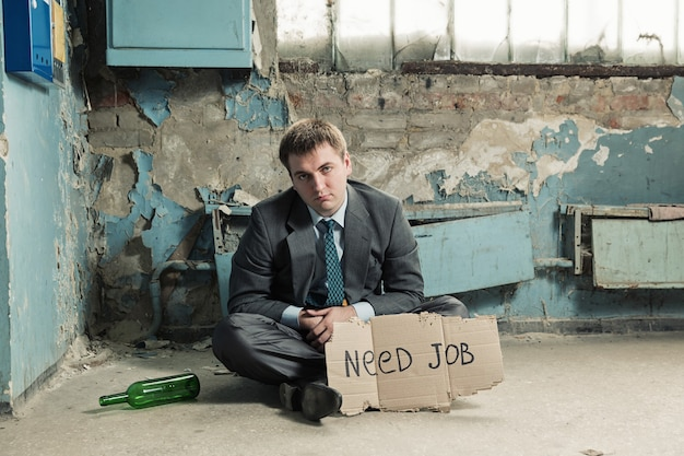 Armer geschäftsmann, der schild hält und um arbeit bittet
