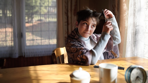 Armes trauriges kleines mädchen, das am tisch sitzt und zu hause haare schneidet, armutskonzept.