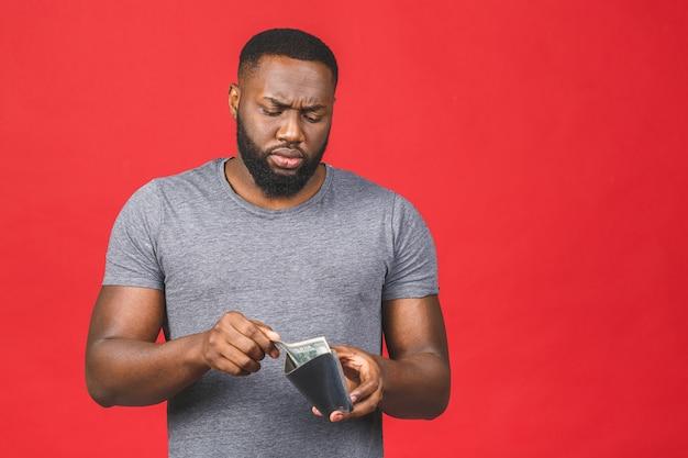 Armutskrisenkonzept. verärgerter junger bärtiger afroamerikanermann im lässigen halten der leeren brieftasche