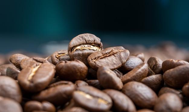Aroma geröstete kaffeebohnen auf dunkelgrün