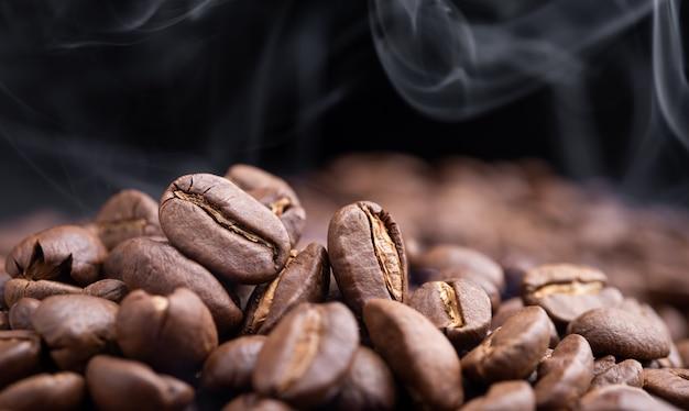 Aroma geröstete kaffeebohnen mit rauch steigt im dunkeln auf