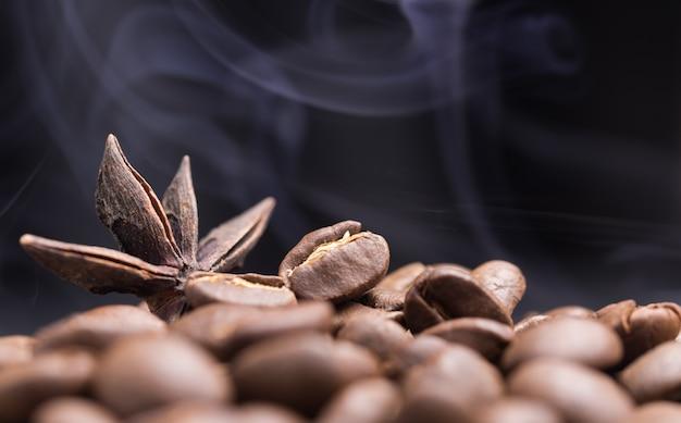Aroma geröstete kaffeebohnen und sternanis mit rauch auf violett dunkel