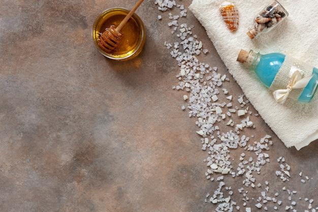 Aroma-meersalz, frischer honig, meeresmineralien, natürlicher kosmetischer lehm und handtuch.