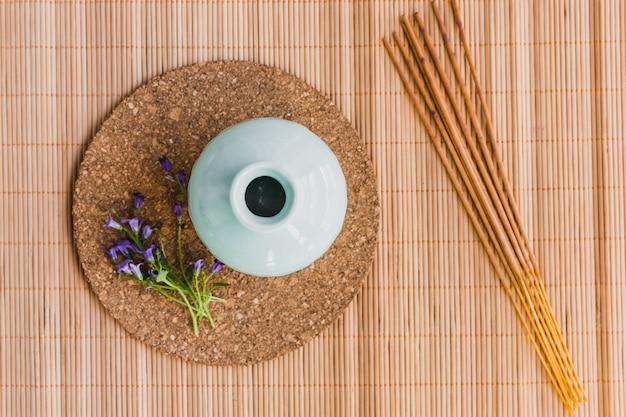 Aroma stöcke und blumen nahe vase