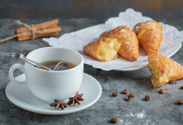 Aroma tasse tee mit leckeren croissants. Kostenlose Fotos