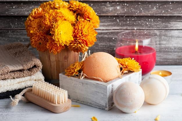Aromabadebomben in spa-zusammensetzung mit orangefarbenen blüten und handtüchern. aromatherapie-arrangement, zen-stillleben mit brennenden kerzen