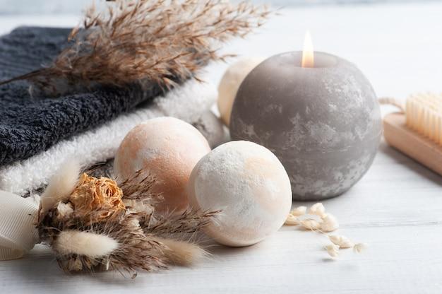 Aromabadebomben in spa-zusammensetzung mit trockenen blumen und handtüchern