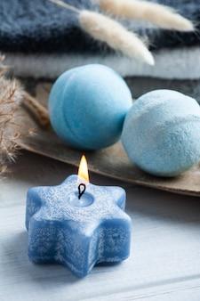 Aromablaue badebomben in spa-zusammensetzung mit trockenen blumen und handtüchern. aromatherapie-arrangement, zen-stillleben mit brennender sternkerze
