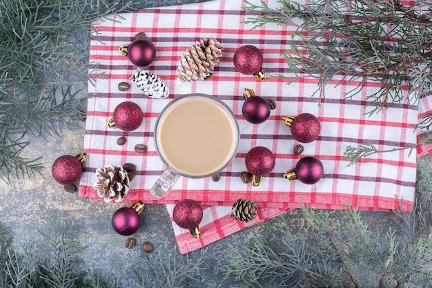 Aromakaffee mit tannenzapfen und weihnachtskugeln auf tischdecke. foto in hoher qualität