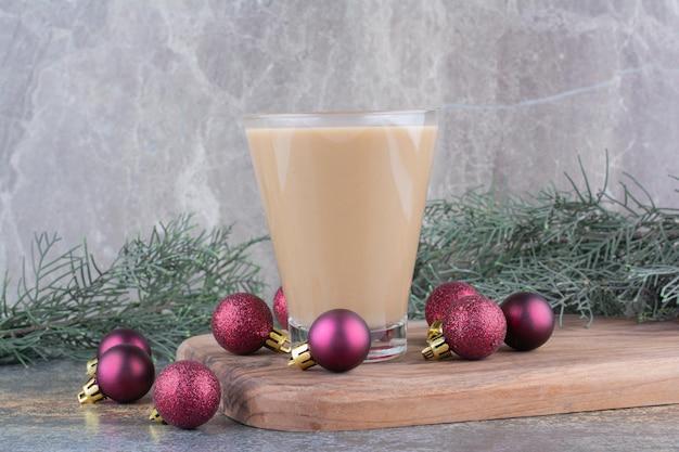 Aromakaffee mit weihnachtskugeln auf holzbrett. foto in hoher qualität