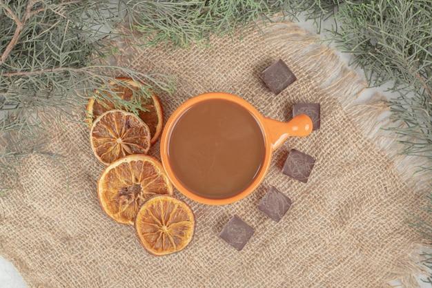 Aromakaffee, orangenscheiben und schokolade auf sackleinen.