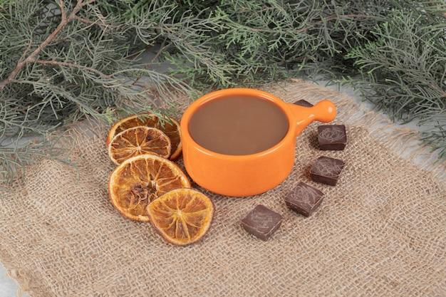 Aromakaffee, orangenscheiben und schokolade auf sackleinen