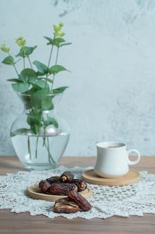 Aromakaffee und köstliche datteln auf holztisch.